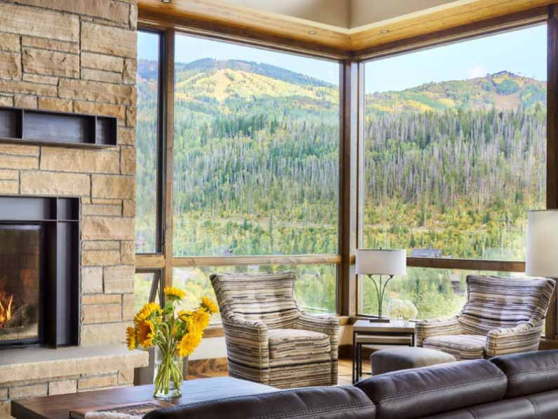 mountain view in autumn from large glass windows in livingroom