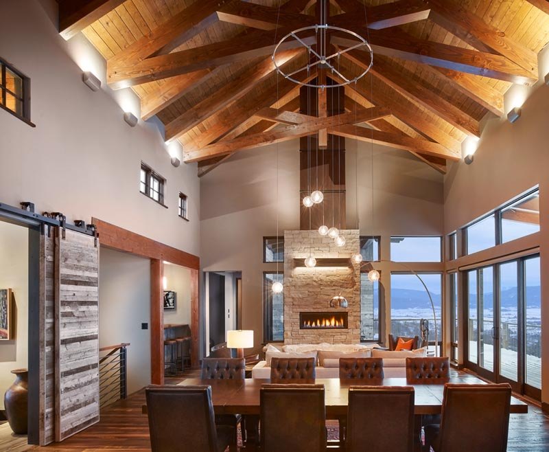 impressive high ceiling cross beams sliding doors and fireplace by gerber berend design build