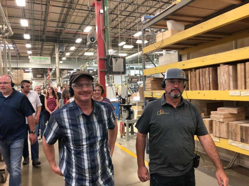 Gerber Berend tour through the wood harbor warehouse with people smiling and wearing protective equipment
